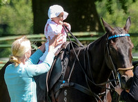 Baby girl on horse holding reigns held by mother