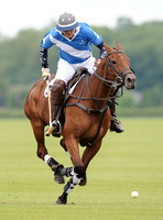 Will Lucas polo action shot, full horse head on, riding towards, Lodge Service colours blue and white.