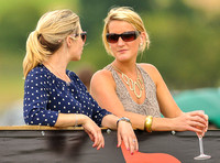two women talking and drinking champagne watching polo match