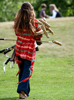 attractive argentine wife walking away from camera carrying armful of polo mallets