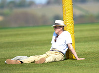 man in panama hat leant against yellow goal post